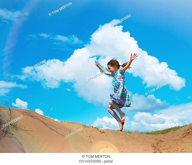 Exuberant girl jumping for joy on beach hill below sunny blue sky with clouds