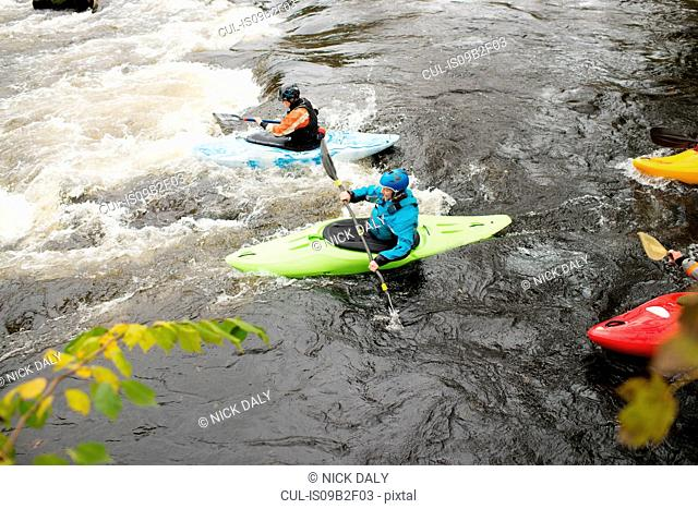 Male and female kayakers paddling to rapids on river Dee, Llangollen, North Wales