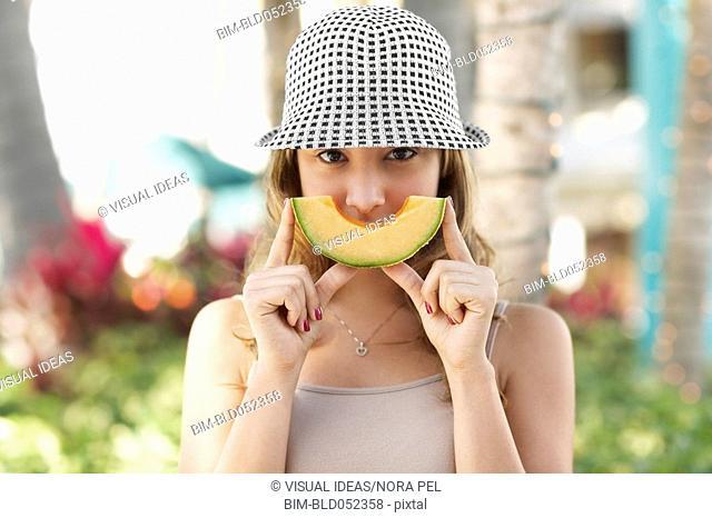 Hispanic woman holding melon slice
