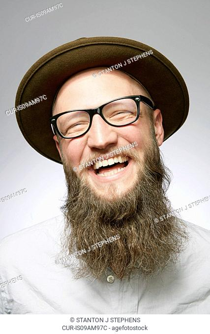 Studio portrait of laughing mid adult man in trilby with overgrown beard