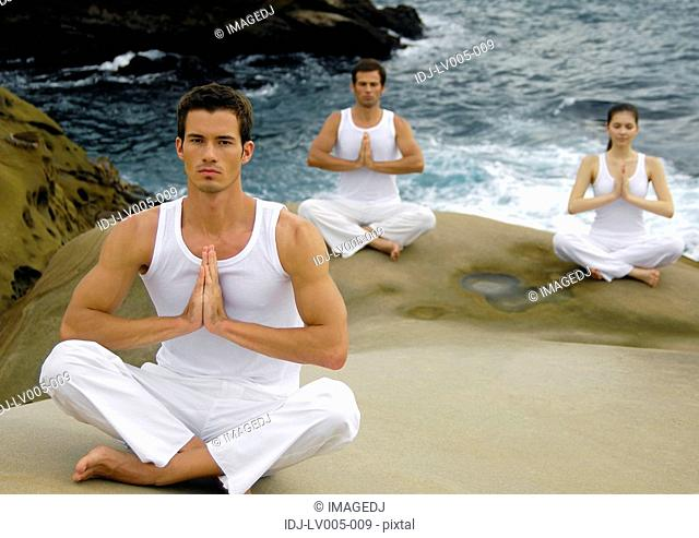 Two young men and a young woman practicing yoga