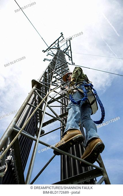 Low angle view of Caucasian worker climbing cellular tower