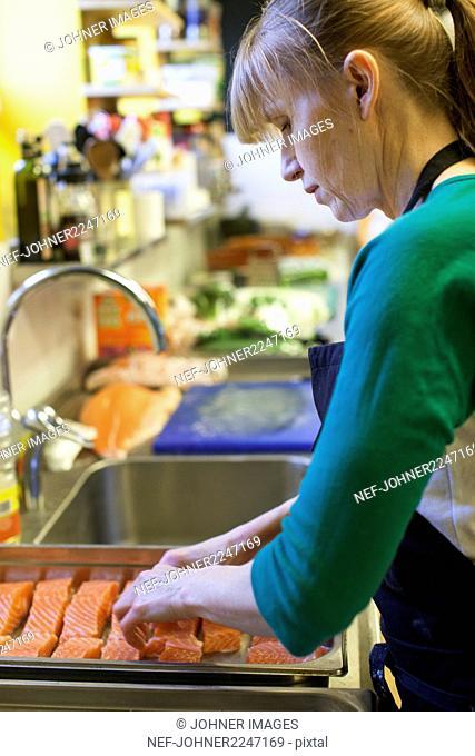 Woman preparing raw salmon