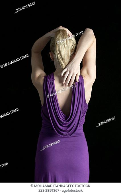 Rear view of a young blond woman wearing a purple dress hands touching hair