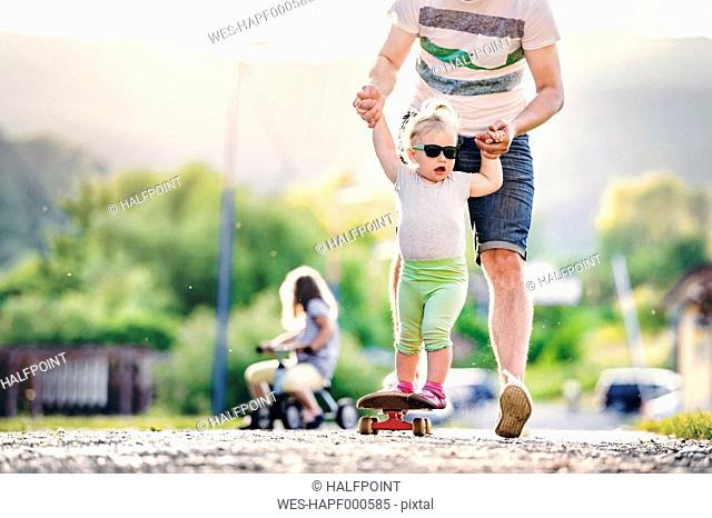 Father and his little daughter having fun with skateboard