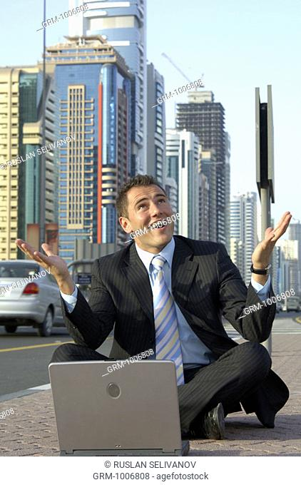 Businessman sitting in tailor seat with laptop on Shaikh Zayed Road in Dubai