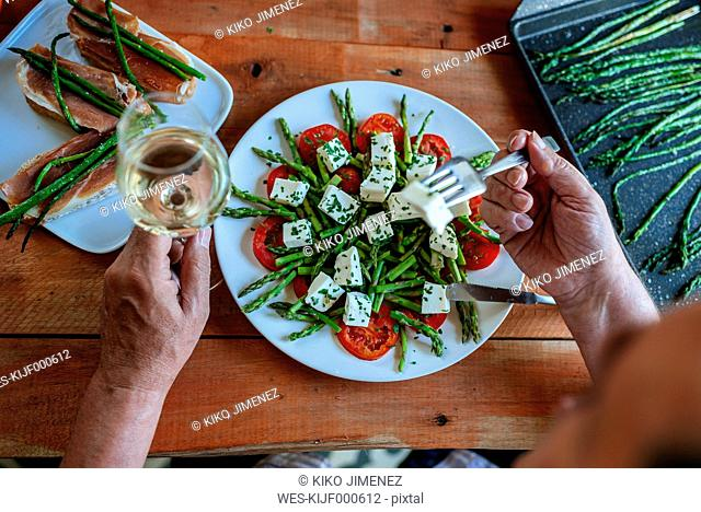 Senior man eating salad of green asparagus, tomatoes and sheep cheese accompanied by white wine