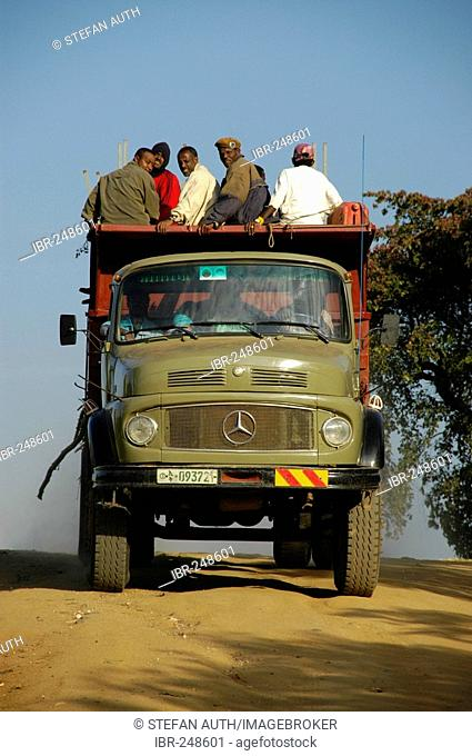 Old Mercedes Benz lorry with passengers sitting on the roof near Jinka Ethiopia