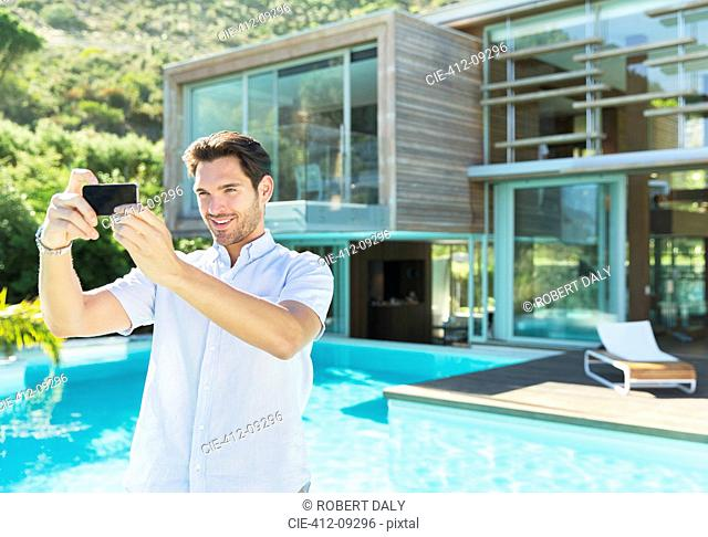 Man taking self-portrait with camera phone at poolside