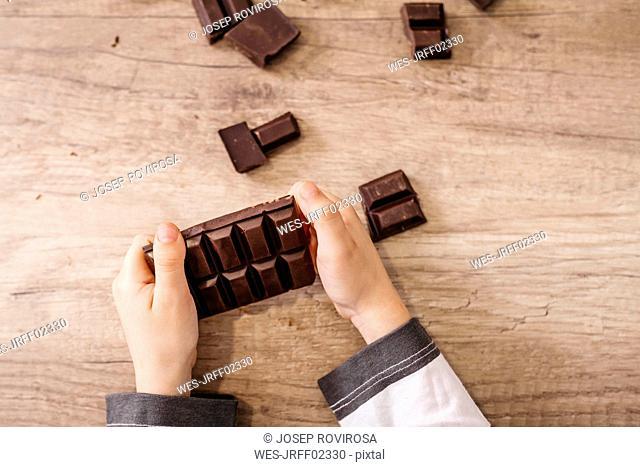 Boy's hands holding chocolate bar, close-up