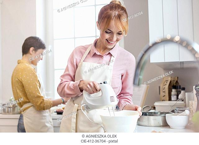 Smiling female caterer baking, using electric hand mixer in kitchen