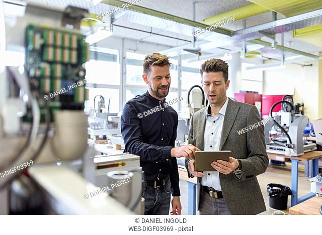 Two businessmen with tablet talking in factory