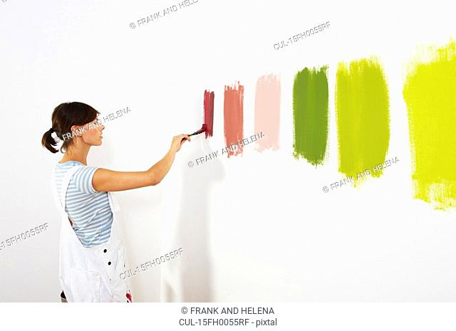 Woman painting colour swatches on wall