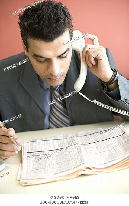 Businessman reading newspaper while on the phone