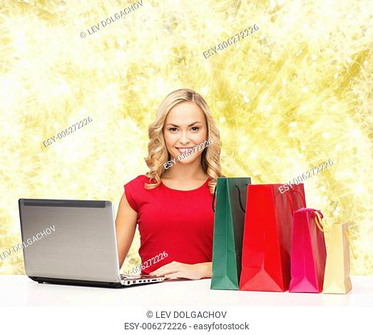 christmas, holidays, technology, advertising and people concept - smiling woman in red blank shirt with shopping bags and laptop computer over yellow lights...