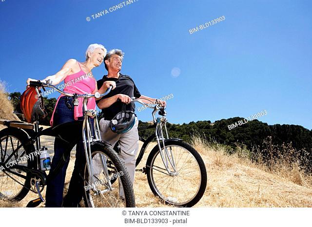 Senior Caucasian couple wheeling dirt bikes on hilltop