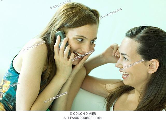 Two young friends smiling at each other, one using cell phone