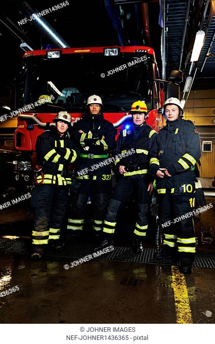 Portrait of fire fighters in front of fire engine