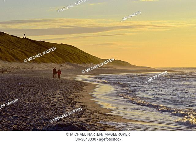 Couple strolling along the sea shore, Wangerooge, Friesland, Lower Saxony, Germany