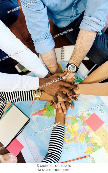 Group of friends stacking hands above world map