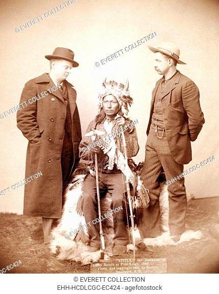 Little, Oglala band leader, full-length studio portrait seated between two men who are standing on either side of him, photograph by John C. H