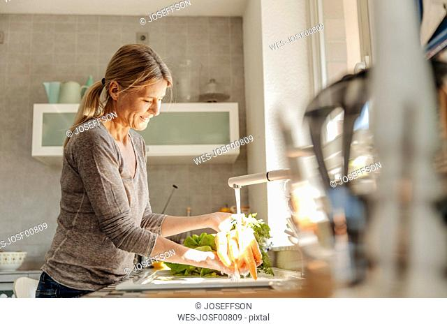 Woman in kitchen washing carrots