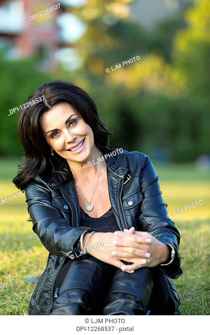 Portrait of a mature woman outdoors in an urban setting in autumn; Edmonton, Alberta, Canada
