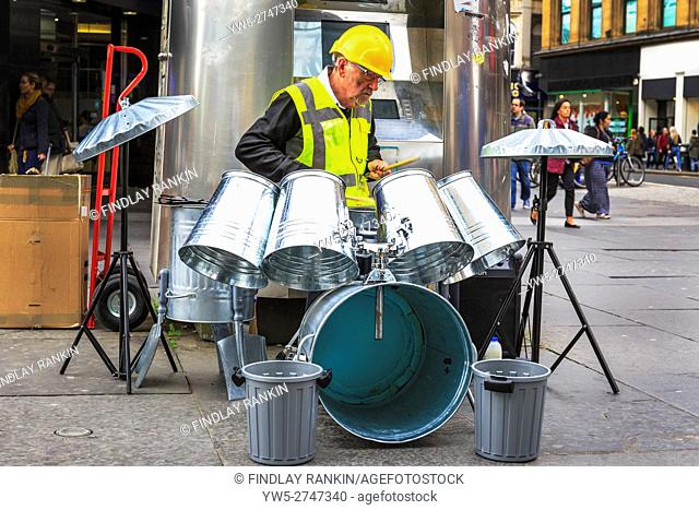 Busker playing in Glasgow, using dustbins as a set of drums, Glasgow, Scotland, UK