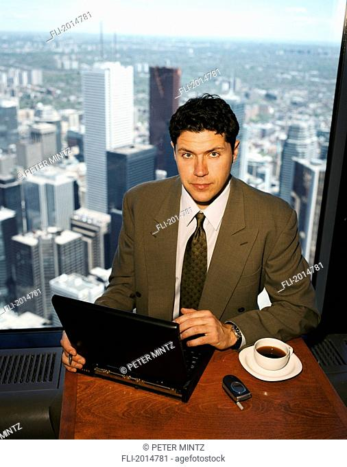 Businessman With Laptop In Front Of Skyline, Toronto, Ontario