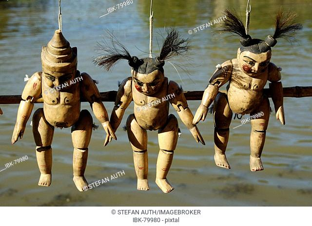 Three wooden puppets above water Inle Lake Shan State Burma