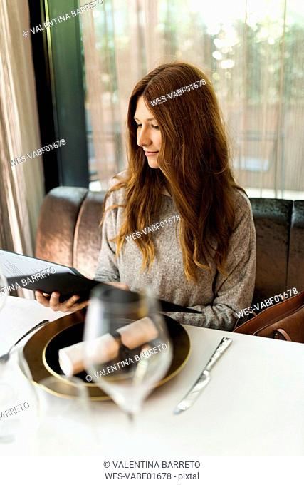 Woman sitting at table in a restaurant reading menu