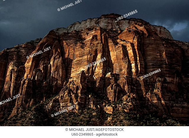 The sun sets on the sheer sandstone canyon walls at Zion National Park, Utah
