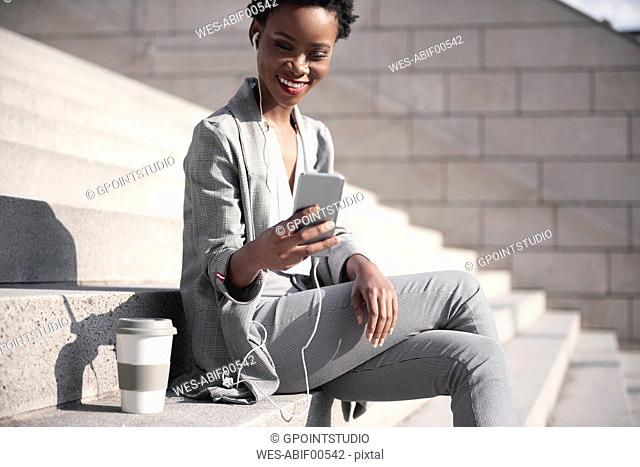Portrait of smiling businesswoman sitting on stairs using earphones and smartphone