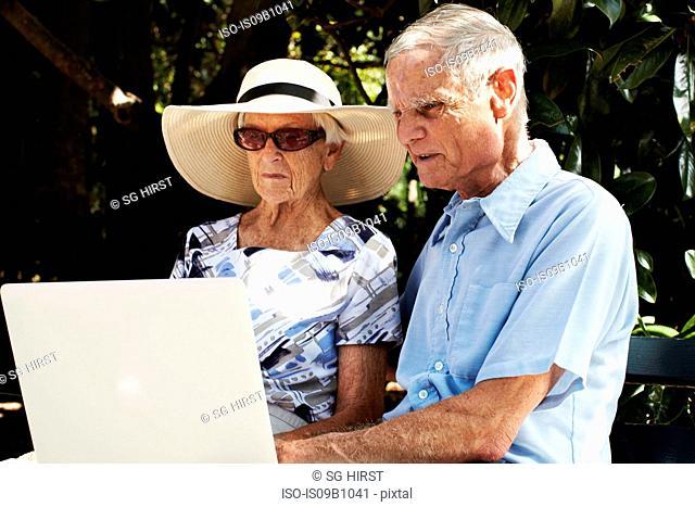 Senior couple sitting using laptop in park