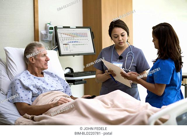 Nurses and patient talking in hospital room