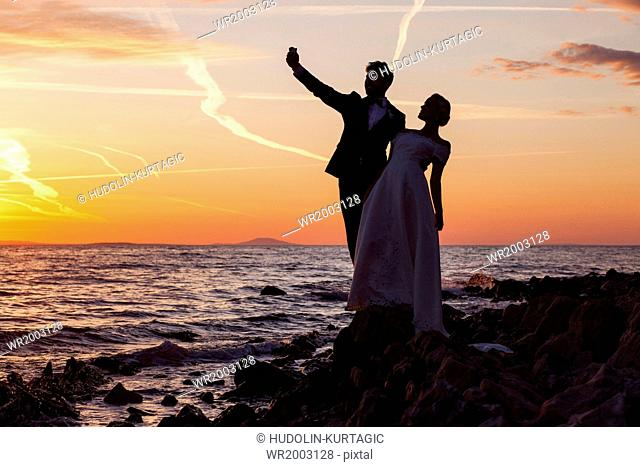 Bride and bridegroom taking photo of themselves at sunset