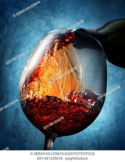 Wine pouring from bottle into a wineglass on blue background