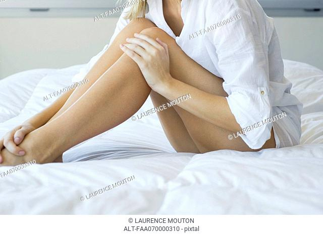 Woman relaxing on bed, touching bare legs