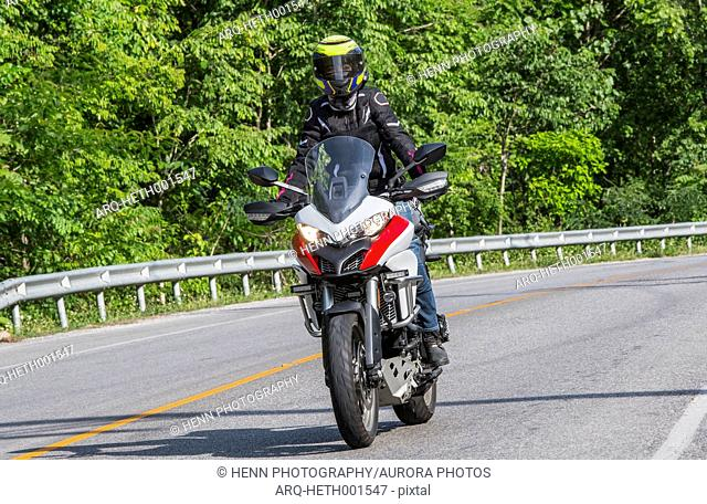 Biker riding along countryside highway surrounded by green trees, Chiang Rai, Mueang Chiang Rai District, Thailand