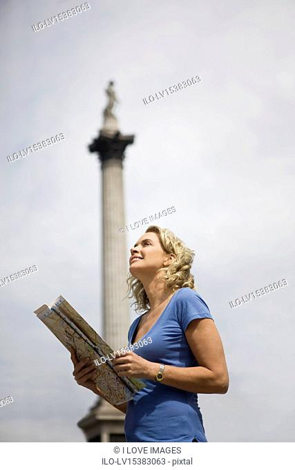 A middle-aged woman standing in Trafalgar Square, looking at a map