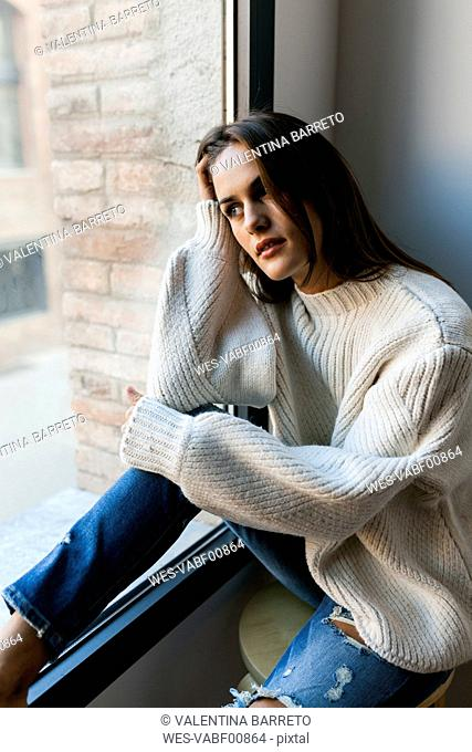 Young woman sitting at a window looking out