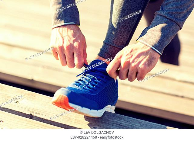 fitness, sport, people and lifestyle concept - close up of sporty man tying shoe laces outdoors