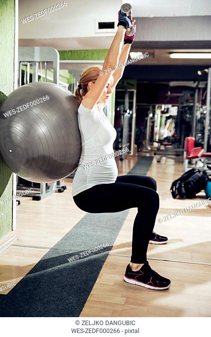 Pregnant woman doing exercises with hand handles and fitness ball in gym