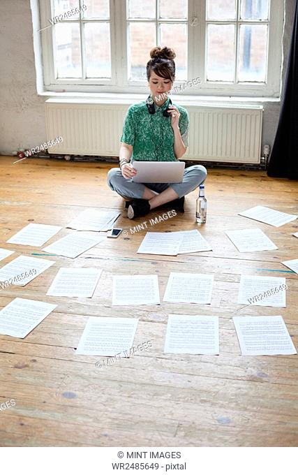 Young woman sitting on the floor in a rehearsal studio, using a laptop computer, looking at sheet music