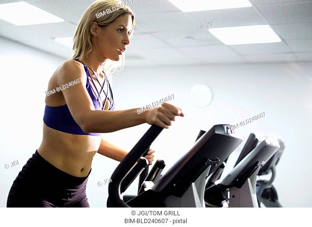 Mixed Race woman using elliptical machine