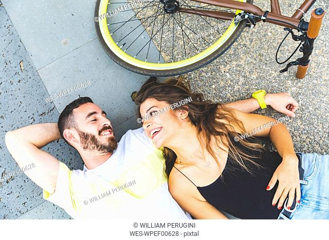 Happy couple lying on the ground next to bicycle and smiling at each other