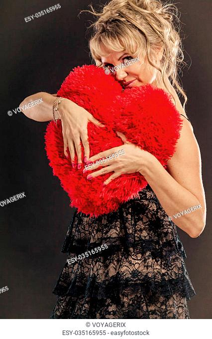 Woman mid aged blonde female wearing black evening dress holding big pillow in form of heart making love symbol from her hands studio shot on black