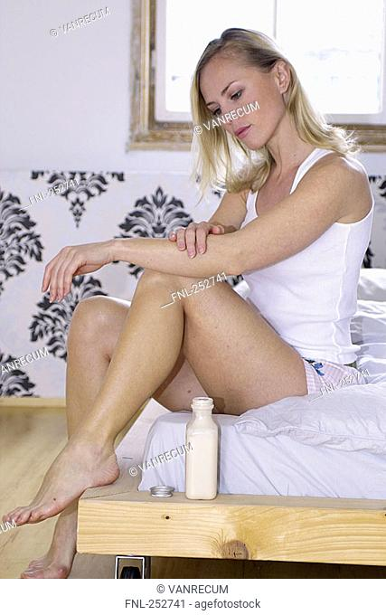 Young woman applying cream on her arms