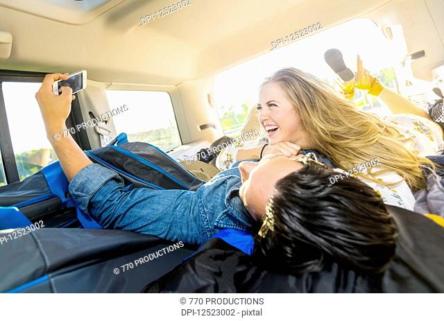 A young couple lays in the back of their vehicle during a road trip talking and laughing together and taking a self-portrait with their cell phone; Edmonton