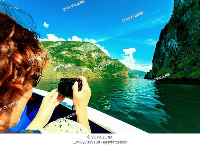 Tourism vacation and travel. Woman tourist taking photo with camera, view from deck of ship on fjord Sognefjord in Norway, Scandinavia